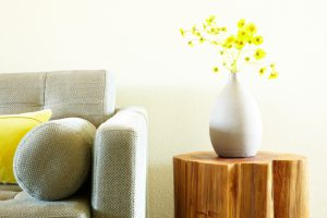 Modern grey sofa and side table with flower arrangement. Front view.