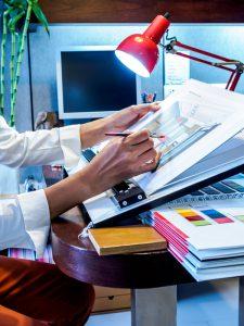 Interior designer's hand working with illustration sketch on desk